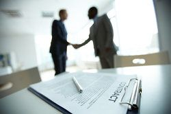 Blurred businessmen shaking hands with contract paperwork and pen in foreground