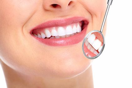 Woman's straight, white teeth and dental examination mirror