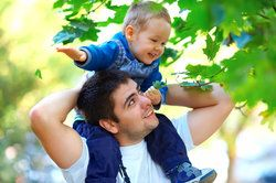 Father playing with toddler on his shoulders