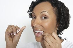 A woman flosses her front teeth.