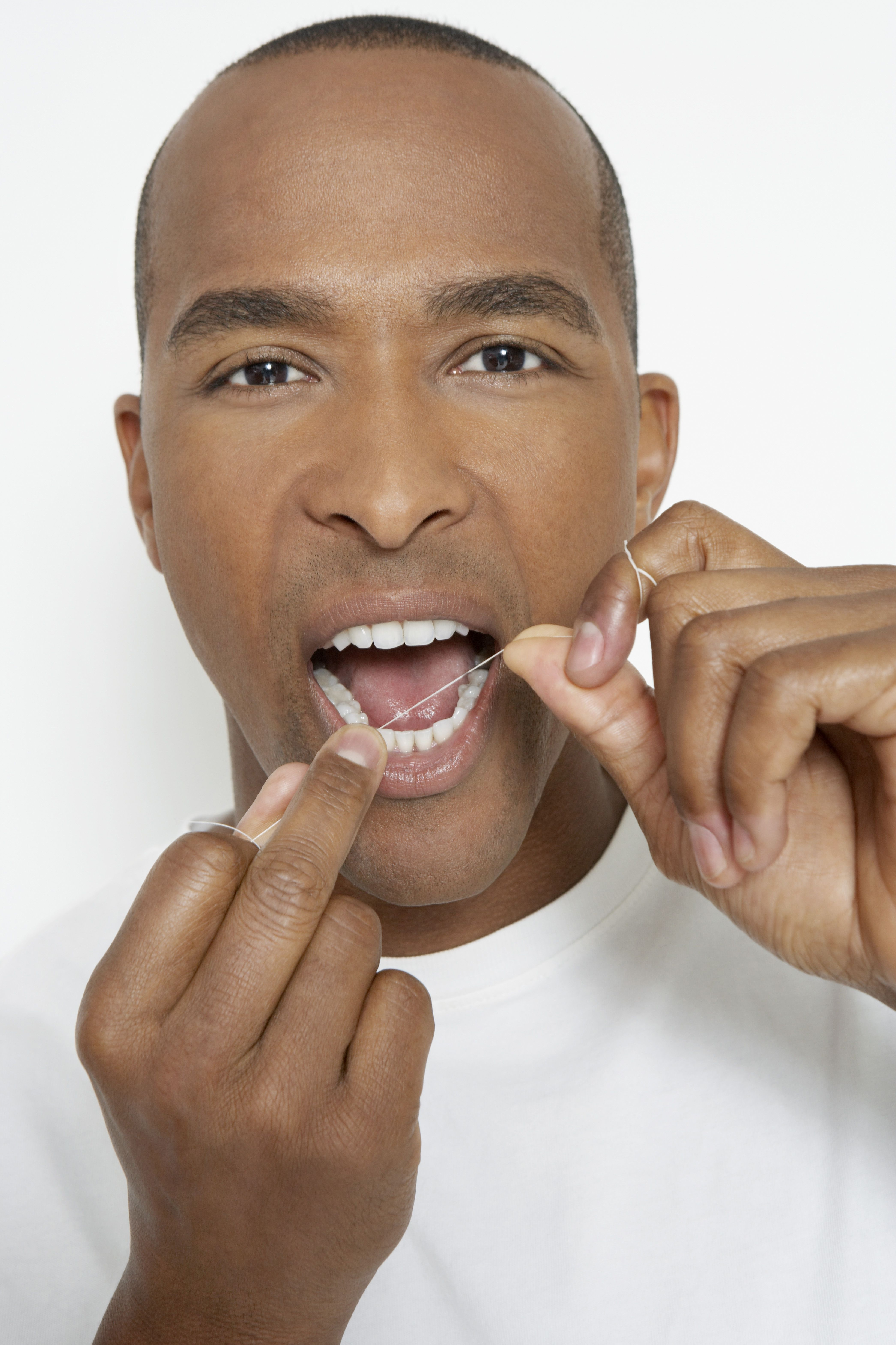 Attractive young man flossing teeth