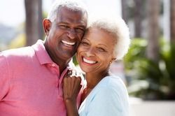 Older couple posing outside cheek-to-cheek
