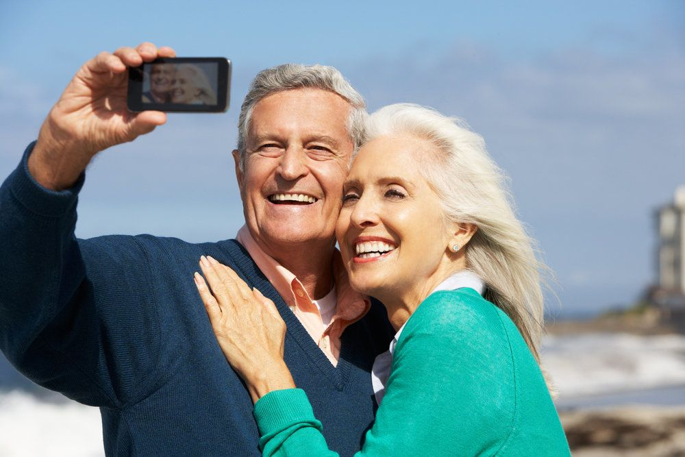 Older couple flashing their healthy smiles while taking a photo of themselves