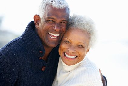 A smiling, middle-aged couple wearing comfortable sweaters smiles joyfully outside.
