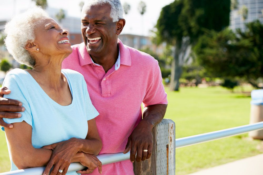 An elderly couple laughing