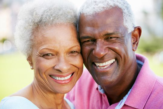 Smiling elderly African American couple with heads together