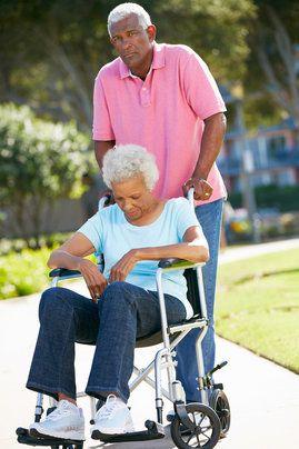 Senior man Pushing Unhappy wife In Wheelchair