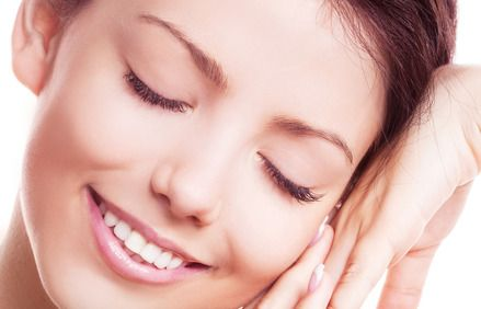 Close view of a smiling young woman facing camera with eyes clothed and head resting on her hand