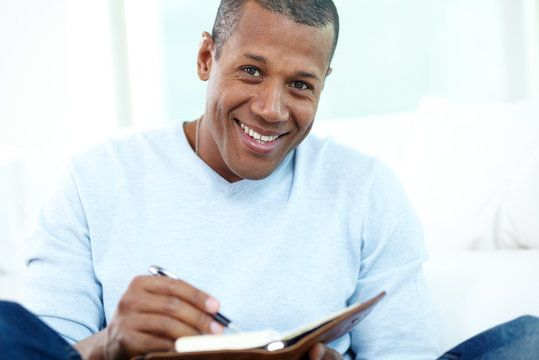 A happy man writing in a journal.