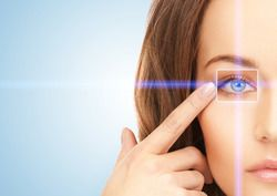 Woman pointing to eye surrounded by computer graphics