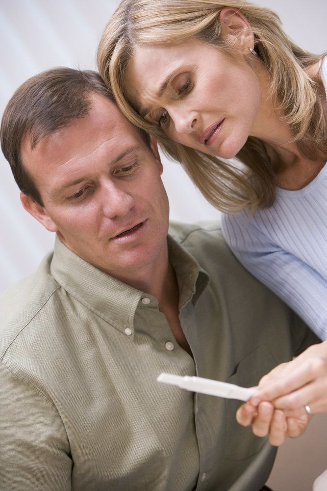 Couple looking at a negative pregnancy test result in disappointment