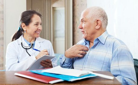 Elderly patient conversing about treatment options with doctor