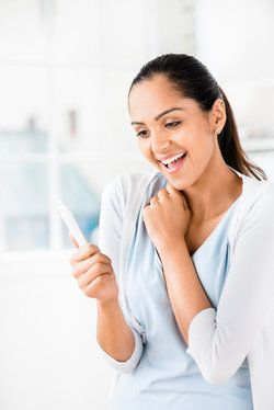 A woman looking happily at a pregnancy test