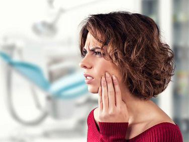 A woman wincing in pain and holding her fingertips to her jaw because of tooth pain.