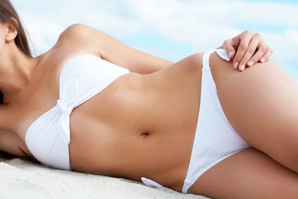 Shapely, slim woman in white bikini laying on side