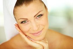 Beautiful smiling woman with hair wrapped in spa towel