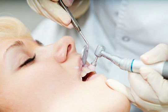 Woman receiving professional tooth cleaning
