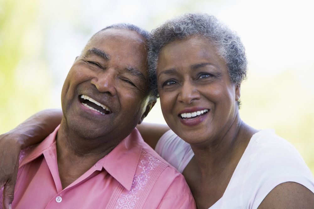 Laughing middle-aged couple smiling for camera