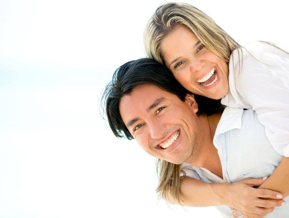 A man and woman with healthy, white smiles