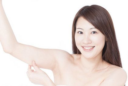 Smiling brunette raising arm and pinching skin on its lower edge