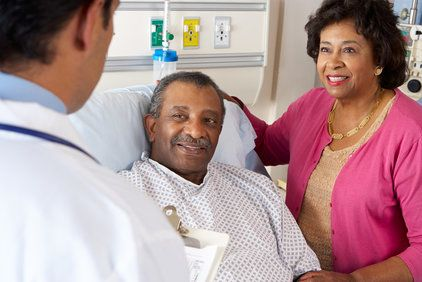 A man in a hospital bed and his wife, standing by, speak with their doctor.