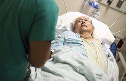 Elderly woman lying in hospital bed talking to nurse