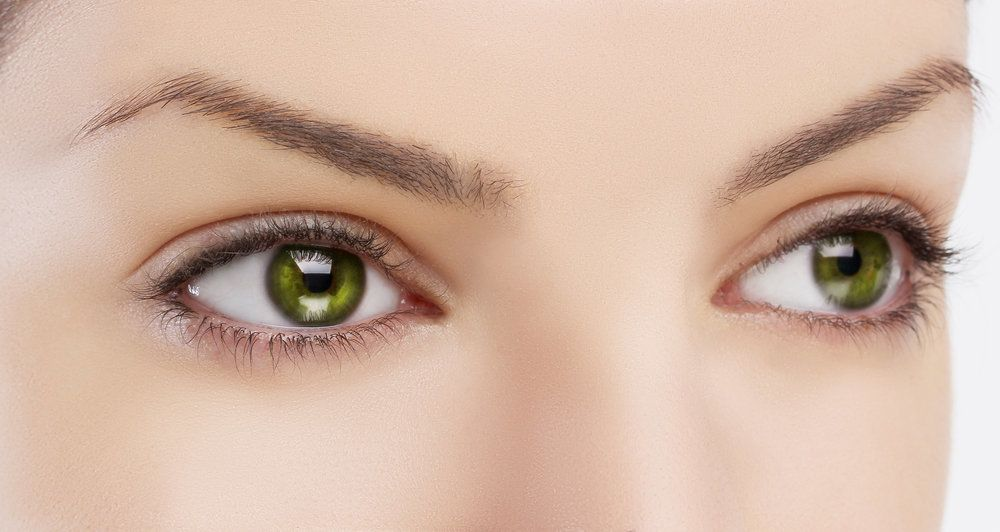 A close-up image of a woman with green eyes