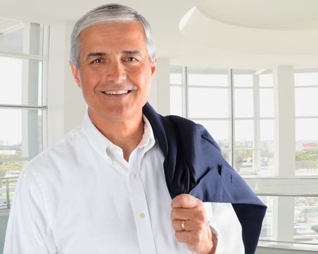 Smiling man with gray hair and business jacket draped over his shoulder