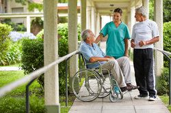 Caucasian man in wheelchair talking with nurse and another man