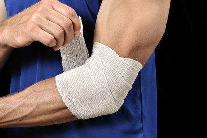 Athletic man wrapping elbow in ace bandage