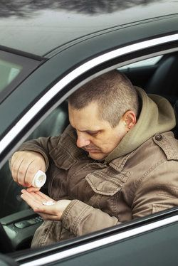 A male driver pouring pills into his hand