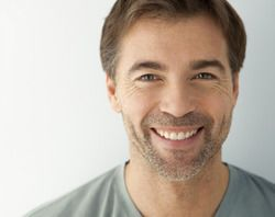 Middle aged smiling man with brown hair and straight teeth