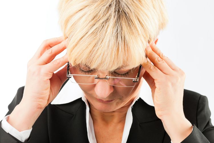 A middle-aged blonde woman winces in pain while holding her temples.