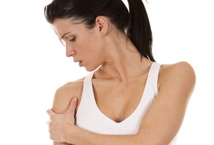 Concerned-looking woman holding shoulder in pain