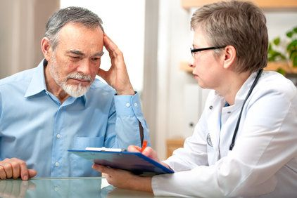 Pensive looking man reviewing paperwork with his doctor