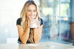 A blonde woman sipping tea and smiling