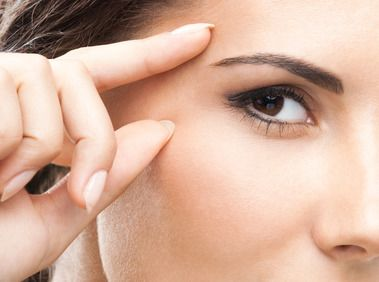 Woman holding fingers on either side of her full eyebrow