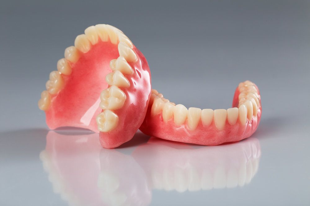 Photo of traditional dentures on gray reflective surface