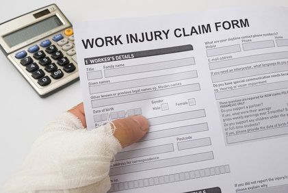 Bandaged hand holding workers' compensation claim paperwork next to calculator