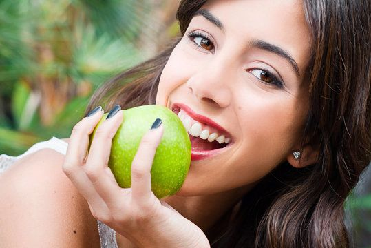 Woman with beautiful teeth biting into an apple.
