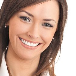 A woman smiling to show straight, white teeth and an even gum line