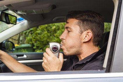 Man blowing into a breathalyzer