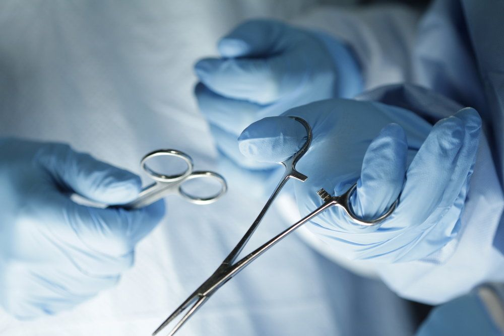 A doctor's hands holding surgical instruments