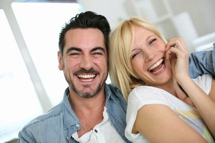 Laughing, attractive couple leaning against one another