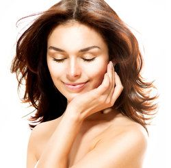 A woman touching her soft facial skin, looking content after nasolabial fold treatment