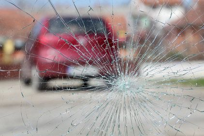 Shattered windshield and blurred car in roadway