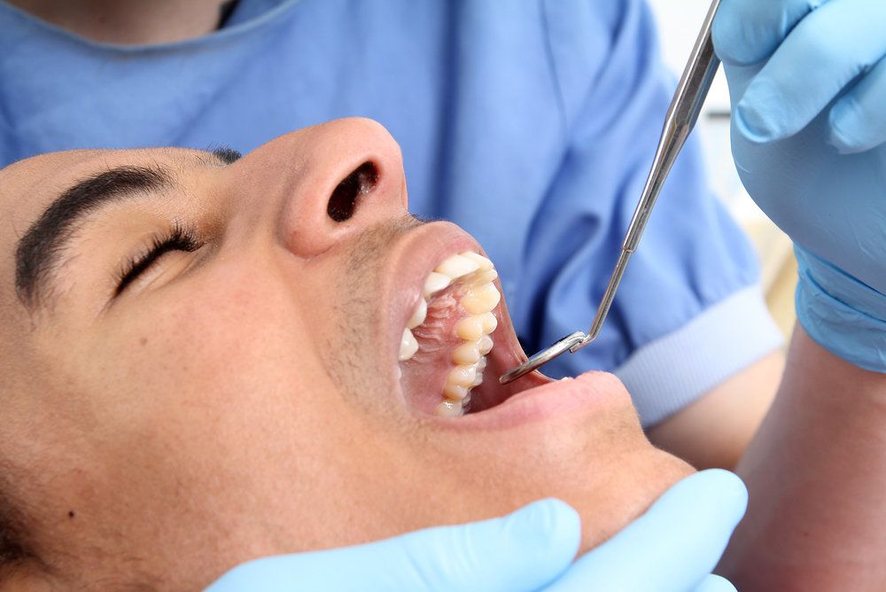 Male having his teeth examined by the dentist