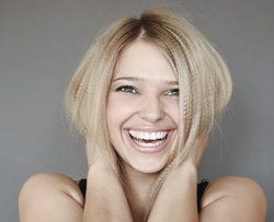 A very happy blonde woman holds her hands behind her neck while smiling.