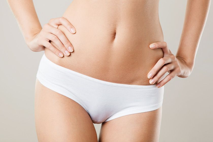 Close-up of a woman's slender abdominal region after tummy tuck post-pregnancy