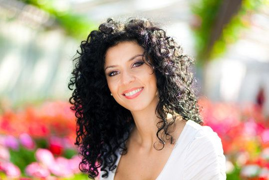 Woman with very curly black hair posing in front of flowers